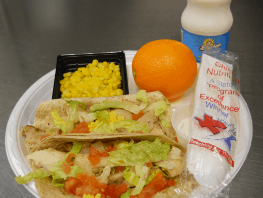 Chicken tacos in a whole grain tortilla with low-fat cheese, lettuce and tomato served with an orange, corn, and fat-free milk