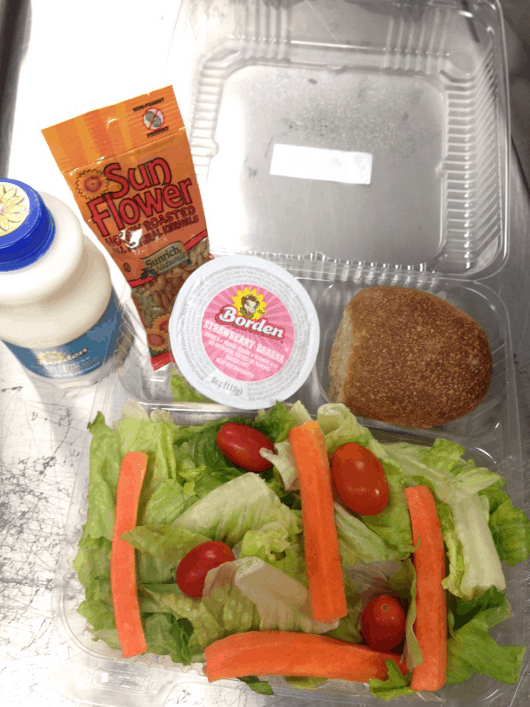 Fresh garden salad with romaine lettuce, carrots and tomato, served with a whole-grain roll, sunflower seeds, a low-fat yogurt and fat-free milk