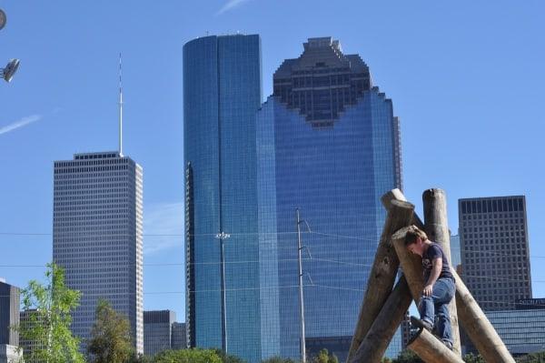 Climbing at by the Houston Skyline Fish Family Play Area Buffalo Bayou Park