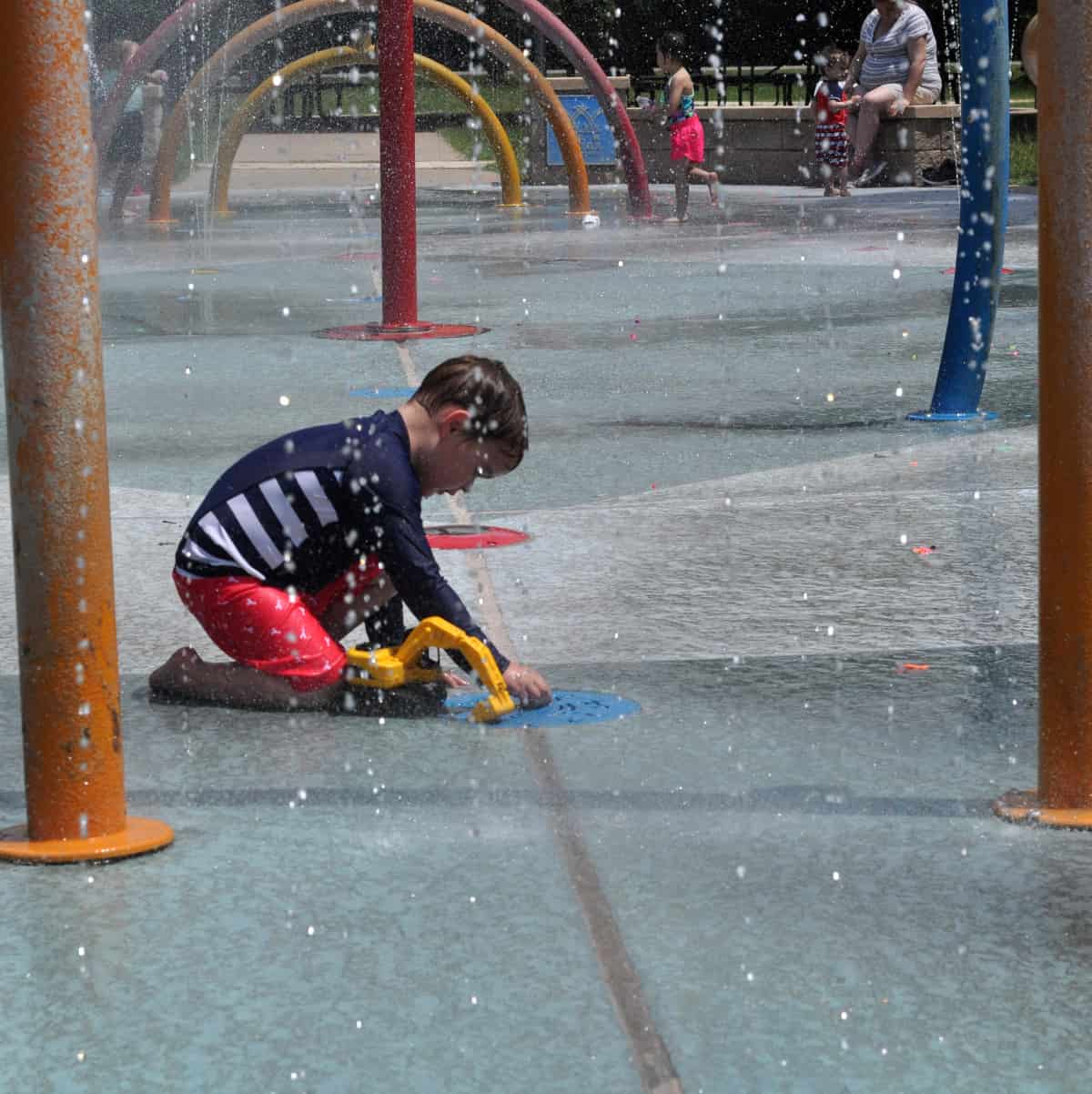 Playing with toy truck at splashpad
